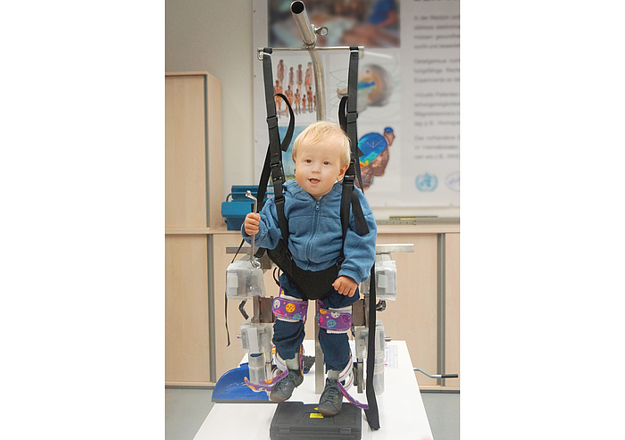 Kind mit Bewegungsstörungen trainiert mit dem Lokomat.