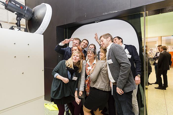 Messebetreuerinnen und -betreuer posieren scherzhaft vor einer Fotobox.