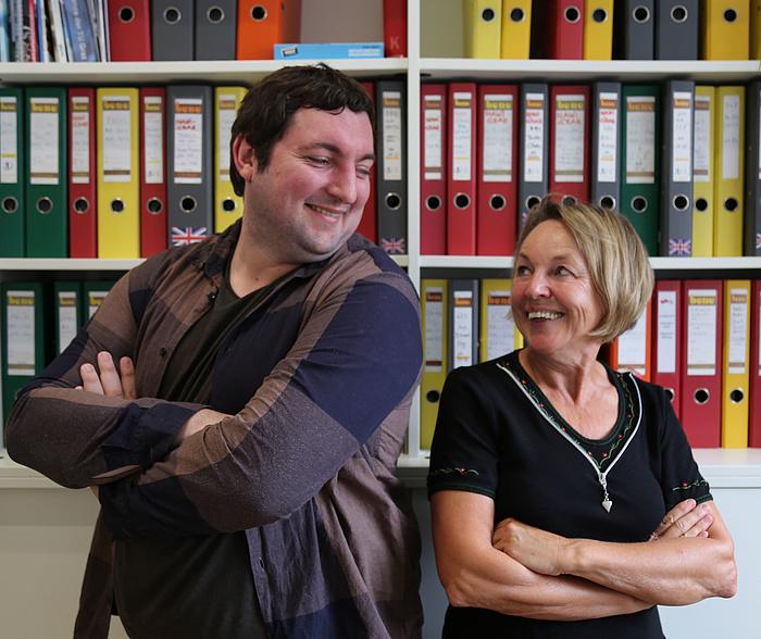 Christian Dobnik und Anna Maria Moisi lachen sich herzlich an - mit verschränken Armen Seite an Seite vor einer Wand von Aktenordnern im Büro an der TU Graz.