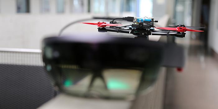 Im Vordergrund eine große schwarze Brille mit durchsichtigen Gläsern, im Hintergrund eine Drohne, also ein schwarzes Gestell mit roten Propellern