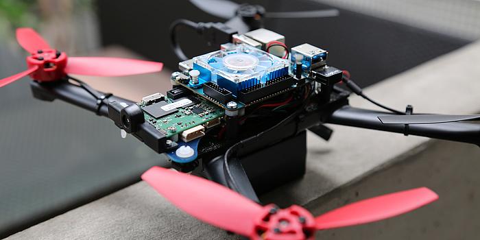 Ein schwarzes Drohnengestell, mit roten Propellern, einem blauen Ventilator und einer grünen Platte mit Schaltungen.