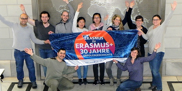 "Staff and international students of TU Graz hold a colourful banner with the inscription ""From Erasmus to Erasmus+ – a story of 30 years."""