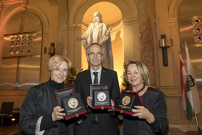 Von links nach rechts: Sybille Mick, Roland Würschum und Anna Maria Moisi zeigen stolz ihre Erzherzog-Johann-Medaillen in der Aula der TU Graz.