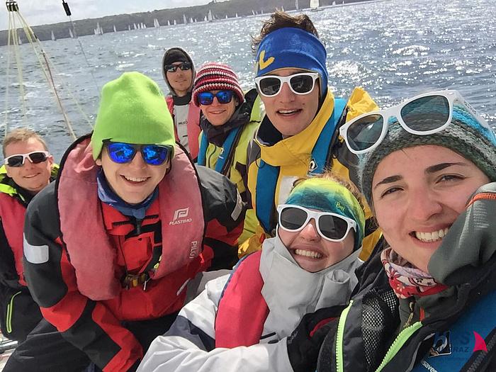 Mit Segelkleigung, Sonnenbrillen, Hauben oder Stirnbändern ausgerüstet strahlen sieben Mitglieder des HPS Teams auf ihrem Boot in die Selfie-Kamera.