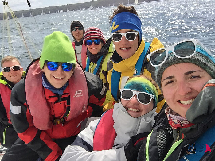 Equipped with sailing clothes, sunglasses, woolly hats and headbands, seven members of the HPS team smiling at the selfie camera on their boat.