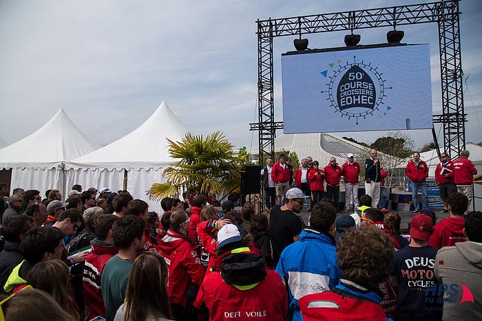 Internationale Studierende vor einer Bühne mit dem riesigen Banner der EDHEC-Segelregatta im Hintergrund.