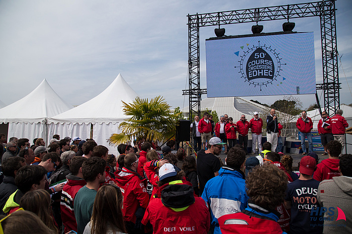 (International students in front of a stage with the huge banner of the EDHEC sailing regatta in the background.