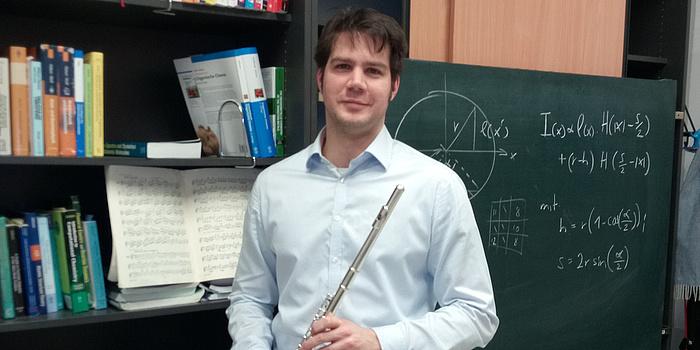Andreas Hauser hält seine Querflöte in der Hand. Hinter ihm im Bücherregal steht ein Heft mit Noten.