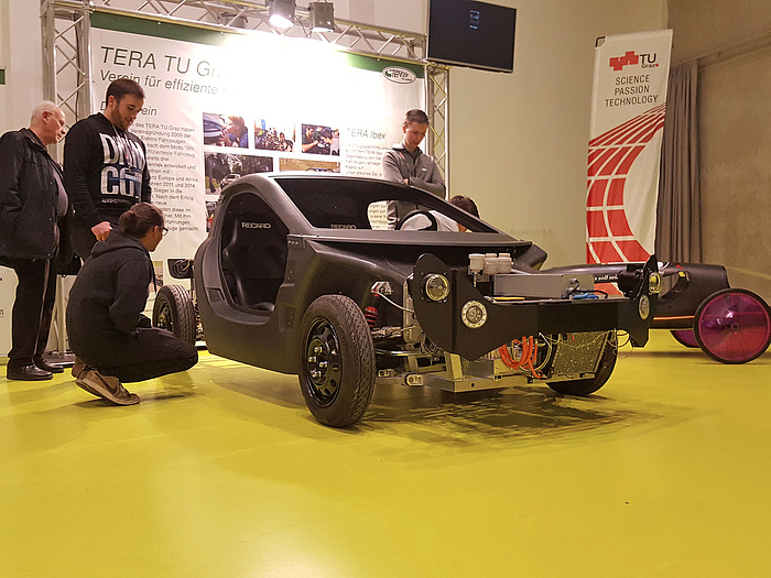 An IBEX model in front of a presentation board of the TERA TU Graz team, surrounded by interested persons looking at the vehicle in detail.