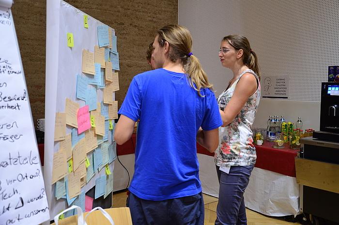 TU Graz-Student Philipp Rouschal (ganz links) mit einer Teamkollegin und einem Teamkollegen vor einer Pinwand voller Ideen beim TU Austria Innovations-Marathon.