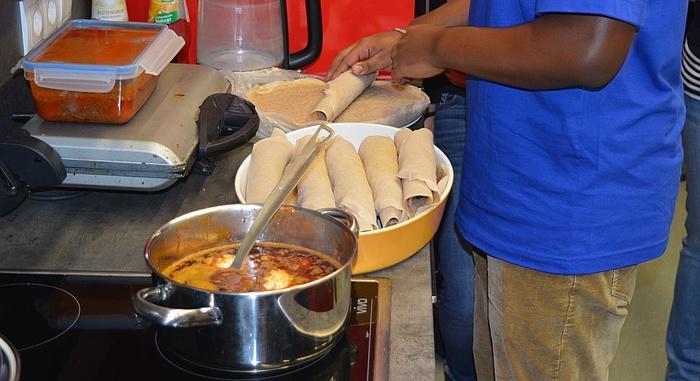 Das äthiopische Gericht Minchet Abish köchelt am Herd während der Koch die Teigfladen einrollt, mit denen das Gericht traditionell gegessen wird.