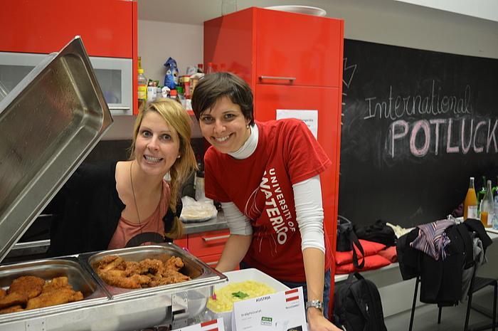 2 junge Frauen, Mitarbeiterinnen des TU Graz-Welcome Centers, öffnen bei einem Kochevent für internationale Studierende gut gelaunt einen Warmhaltebehälter mit Schnitzeln.