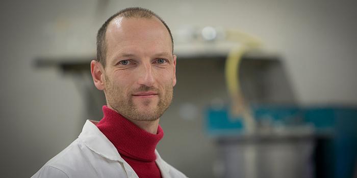 TU Graz-Wissenschafter Joachim Juhart vom Institut für Materialprüfung und Baustofftechnologie mit angeschlossener TVFA für Festigkeits- und Materialprüfung. Porträtfoto mit Labormantel und rotem Rollkragen.