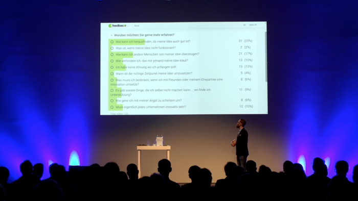 ein Vortragender präsentiert die feedbackr-App vor Publikum.