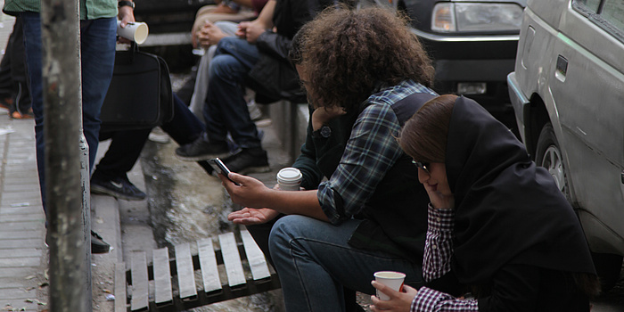 Menschen sitzen an einem kleinen Kanal und trinken Kaffee.