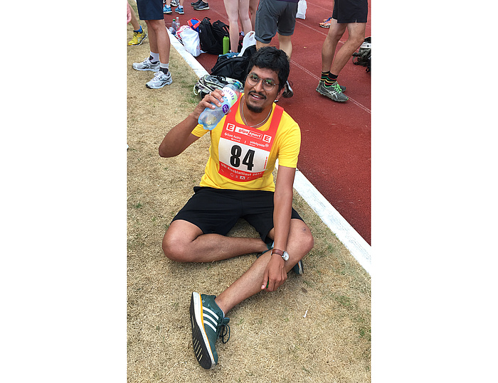Exhausted but happy runner wearing a yellow shirt showing the start number 84 drinks from a bottle of water.