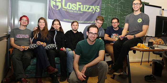 Acht LosFuzzys-Teammitglieder im Fuzzylab, im Hintergrund eine voll beschriebene Tafel und die violette LosFuzzys-Fahne.