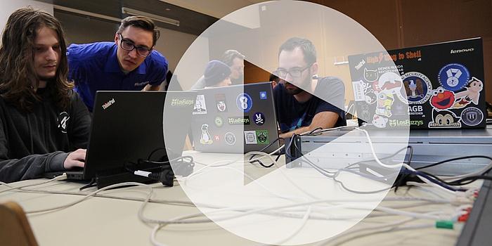 Drei junge Männer sitzen vor ihren Laptops. In der Mitte des Bildes ist ein Pfeil, also ein Play-Button für Videos, zu sehen.