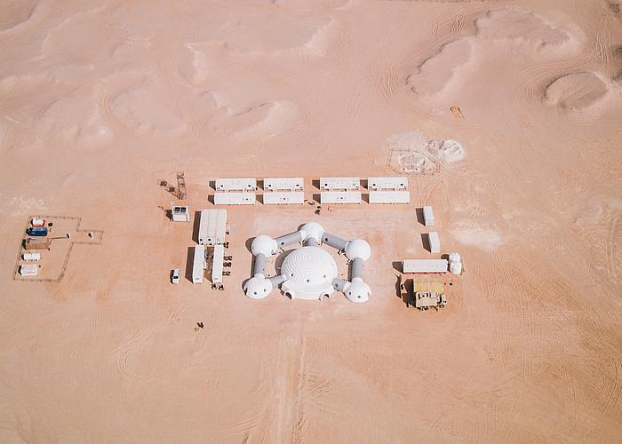 Luftaufnahme der Station, man sieht Wüstensand und die Station im Zentrum umgeben von weißen Containern.