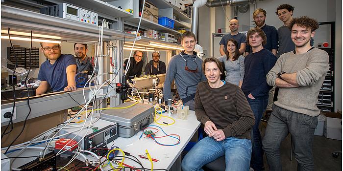 Eine Gruppe von Forschern steht um einen Arbeitstisch in einem bunten und vollgeräumten Labor