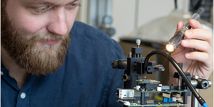 Ein Forscher leuchtet mit einer Taschenlampe auf einen Sensor, der an einem Gestell befestigt ist.