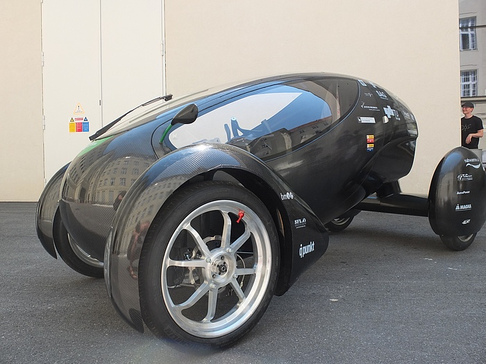 Small black egg-shaped vehicle, becoming increasingly narrower towards the end, with elegant, elongated oval windows, two big wheels at the front and a very wide wheel axle and smaller wheels at the rear.