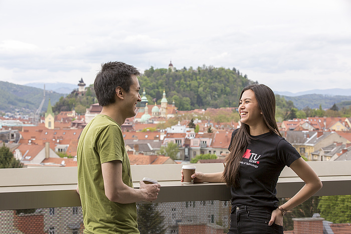 A male student in a green T-shirt and a female student in a black TU Graz shirt talk over coffee, standing on a terrace with a summery Graz Schlossberg in the background.
