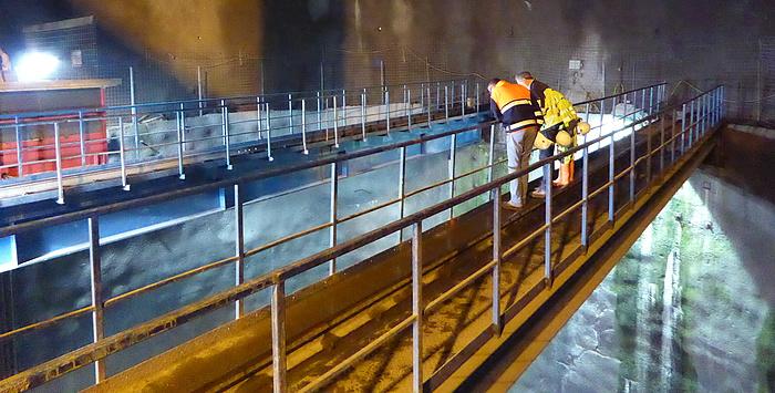 Zwei Arbeiter, die in den Steigschacht des Pumpspeicherkraftwerks Obervermuntwerk 2 blicken.