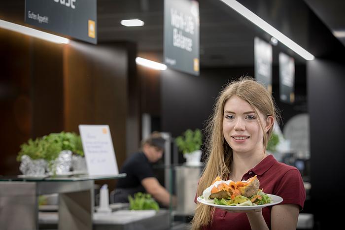 Eine Studentin im weinroten Poloshirt präsentiert ihren Teller samt Ofenkartoffel und Gemüsebeilage vor der Essensausgabe in der Mensa Inffeldgasse.