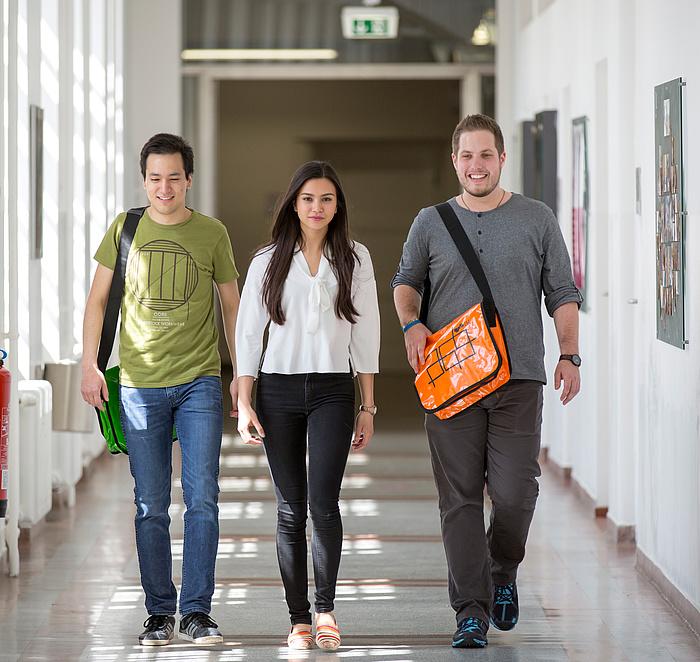 Zwei Studenten und eine Studentin der TU Graz gehen zielstrebig durch den Gang eines Universitätsgebäudes, dem Betrachter entgegen.