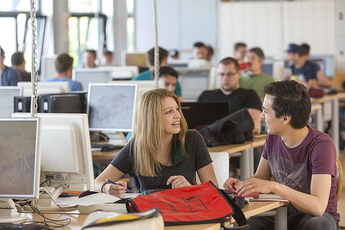 Eine Studentin und ein Student unterhalten sich in einem der Zeichensäle der TU Graz. Im Hintergrund arbeiten Studierende an PCs.