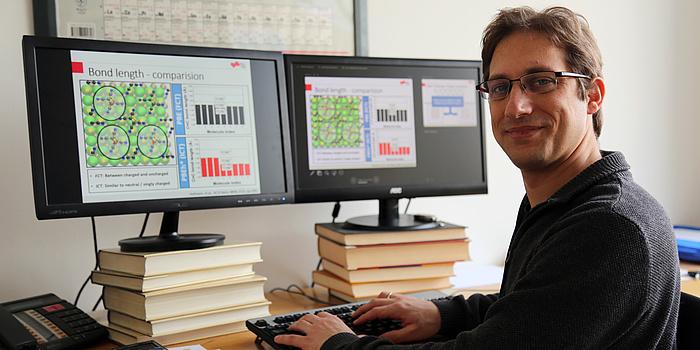Ein Mann sitzt an einem Computer. Vor ihm zwei Computerbildschrime mit einer Grafik aus grünen und schwarzen Kugeln.