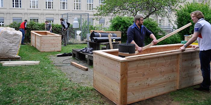 Zwei hölzerne Hochbeete werden von fünf Helfern aufgebaut.