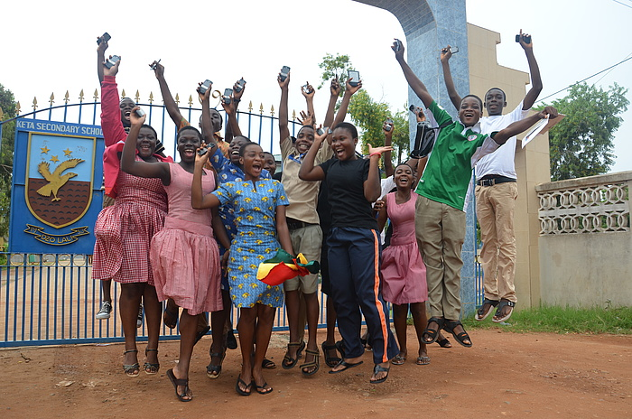 A group of students jumping up into the air in the open against the background of the iron access gate which bears the KETASCO logo.