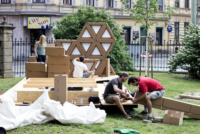Die Architekturstudierenden Patrick Ernst und Robert Sterzing (v.l.) bauen eine Notunterkunft aus Wellkarton auf.