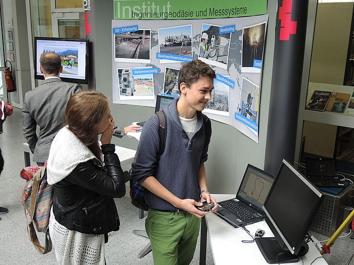 Junge Frau und junger Mann amüsieren sich vor einem Laptop mit einer grafischen Darstellung am geoday2015@TU Graz.