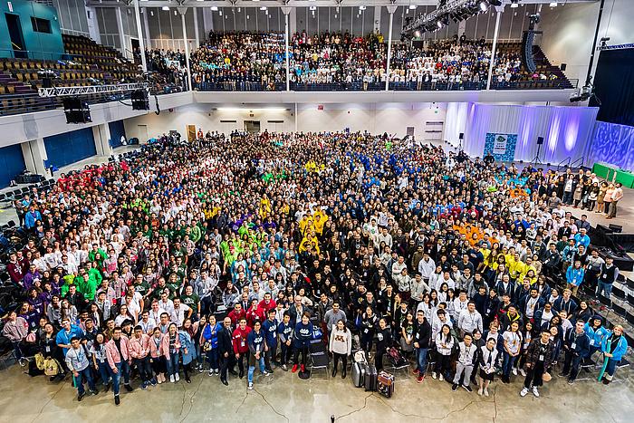 Gruppenfoto der rund 3000 teils in bunte Teamdresses Teilnehmerinnen und Teilnehmer von iGEM.