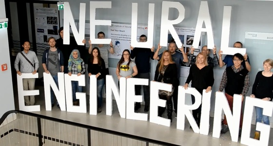 INE team members holding letters and forming the word Neural Engineering. Group photo.