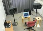 Ein Raum mit Stuhl der von mehreren Lautsprechern in unterschiedlichen Positionen beschallt wird.