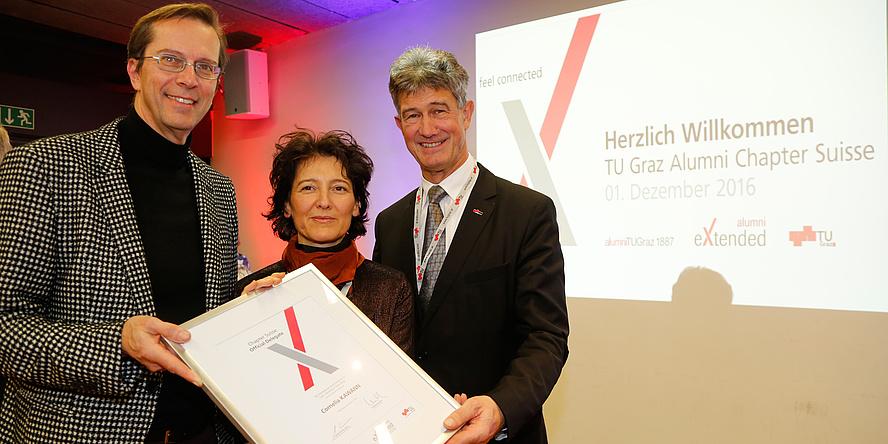 [Translate to Englisch:] Rektor Kainz, Cornelia Kawann und Emo Welzl halten die Grndungsurkunde des neuen Alumni Chapters in die Kamera
