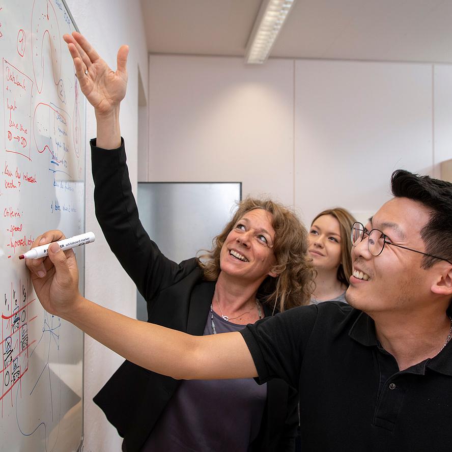 Lehrende und Studierender vor einem Whiteboard