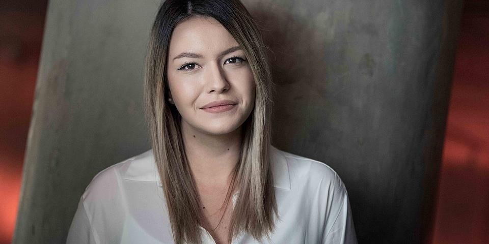 Porträtfofo einer jungen Frau in weißer Bluse.