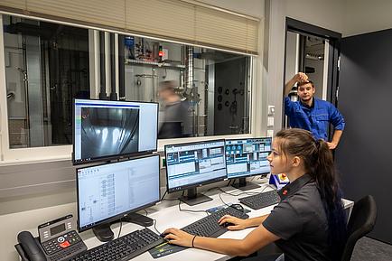 Technikerin und Techniker bei einem Bedienpult