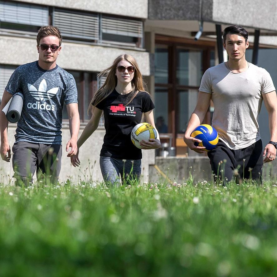 3 junge Leute mit Sportbällen