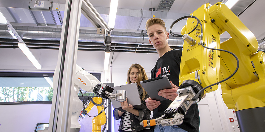 Two students working with a robotic arm.