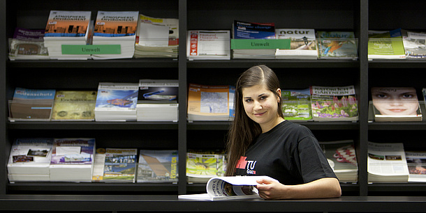 A woman in standing in front of a shelf of journals and paging through a journal.