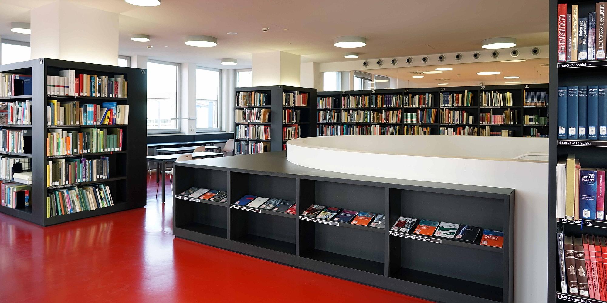 Lesesaal mit Bücherregalen, Tischen und Stühlen