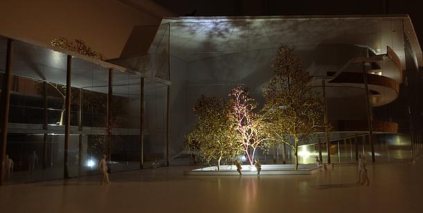 Architekturmodell eines Hauses, davor steht eine Baumgruppe - das Ensemble wir lichttechnisch bespielt.