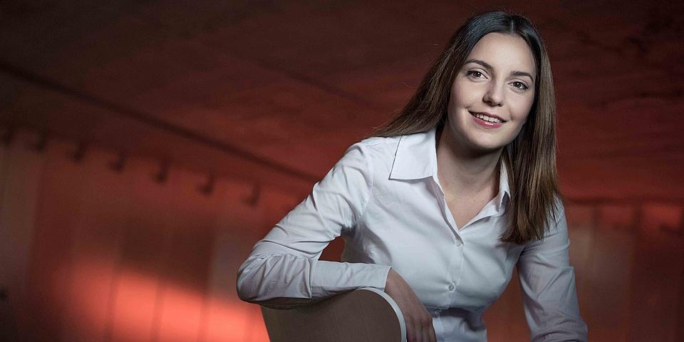 Junge Frau mit weißer Bluse vor einer rötlich beleuchteten Wand