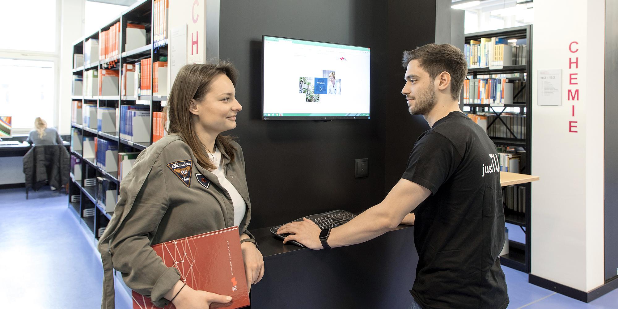 Eine Studentin und ein Student stehen an einem Bildschirm in einer Bibliothek.